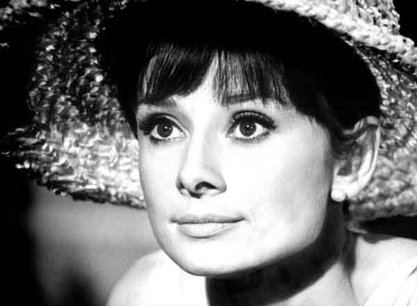 Primo piano della bellissima Audrey Hepburn grandi occhi scuri bellissima bocca con labbro superiore meno evidente nasino perfetto, ha la frangetta e un cappello