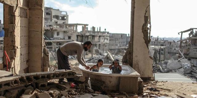 Gaza, il bagno tra le macerie. Una foto per restare umani