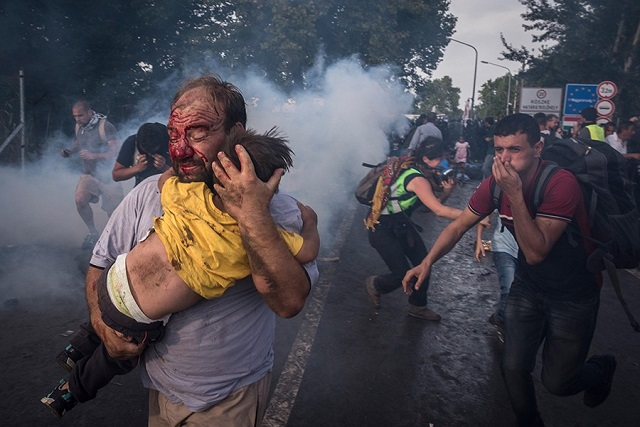 Fonte: Un uomo scappa proteggendo la figlia dagli scontri con la polizia a Horgos, frontiera tra Serbia e Ungheria. Sergey Ponomarev
