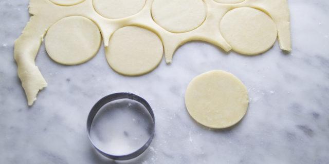 Accendete il forno a 180°. Togliete l'impasto dal frigorifero e stendete l'impasto su un piano di lavoro, leggermente infarinato, aiutandovi con un mattarello fino a raggiungere uno spessore di circa 4mm. Utilizzando uno stampo per biscotti (o un bicchiere) ritagliate dei dischi di impasto.