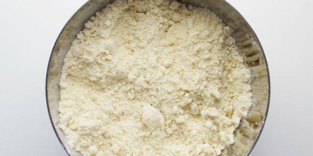 In una ciotola unire la farina con il burro a cubetti e sbriciolate il tutto con le mani fino a ottenere un composto sabbioso.