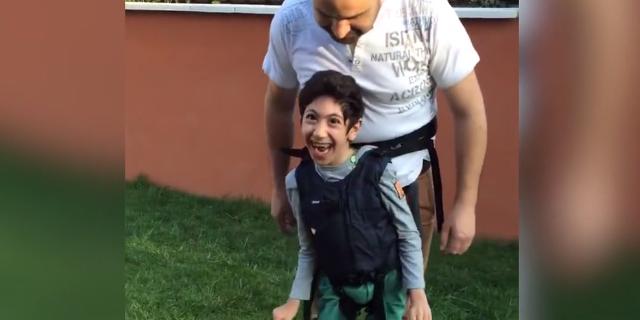 Un padre si inventa il modo per far giocare a calcio il figlio paralizzato: la reazione del ragazzo è emozionante